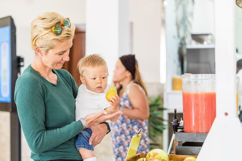 Mother with baby boy choosing pear in all inclusive restaurant stock image