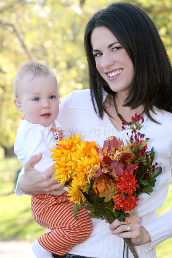 Mother and Baby Boy with Flowers - Fall Theme. Portrait of a young mother and her blue-eyed baby boy with bright orange and yellow flowers, outdoors in a park royalty free stock images