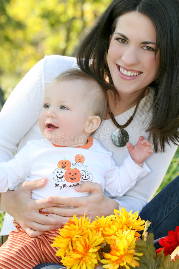 Mother and Baby Boy with Flowers - Fall Theme. Portrait of a young mother and her blue-eyed baby boy with bright orange and yellow flowers, outdoors in a park stock image