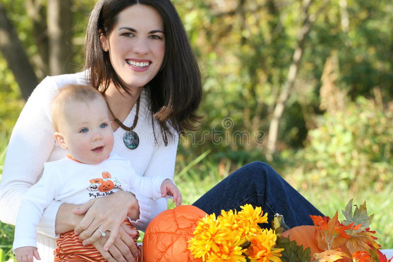 Mother and Baby Boy with Flowers - Fall Theme. Portrait of a young mother and her blue-eyed baby boy with bright orange and yellow flowers, outdoors in a park stock photo
