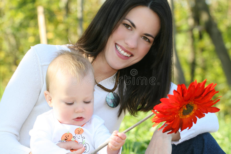 Mother and Baby Boy with Flowers - Fall Theme. Portrait of a young mother and her blue-eyed baby boy with bright orange and yellow flowers, outdoors in a park stock photos