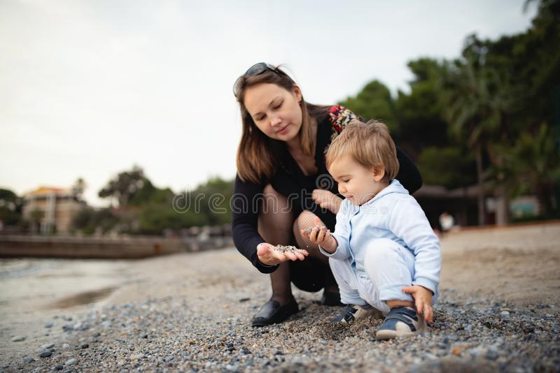Mother and Baby Boy Playing Together At the Seaside. Happy Mother and Baby Boy Playing Together At the Seaside stock photography