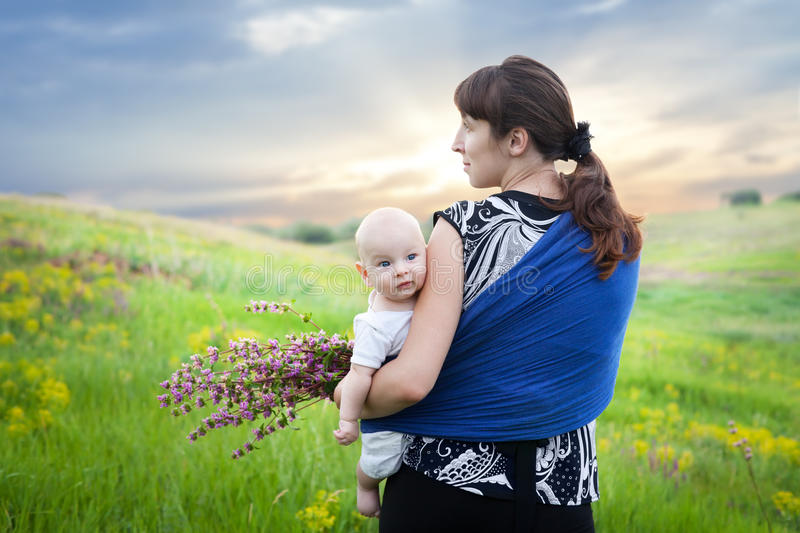 Mother and baby boy in sling on green meadow. Collect flowers at sunset in the summer stock images
