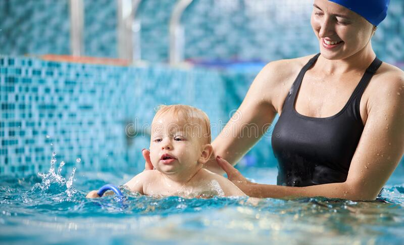 Mother with baby boy in swimming pool training royalty free stock image
