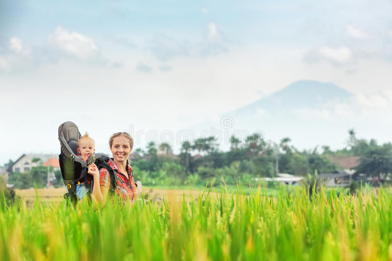 Mother with baby in carrying backpack walking on rice terraces stock image