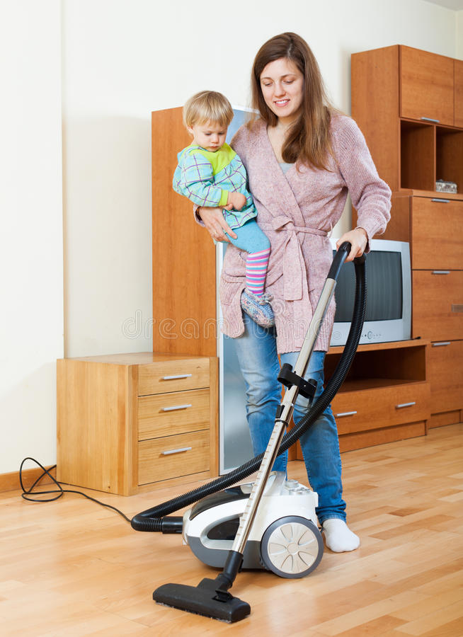Mother with baby cleaning home royalty free stock images