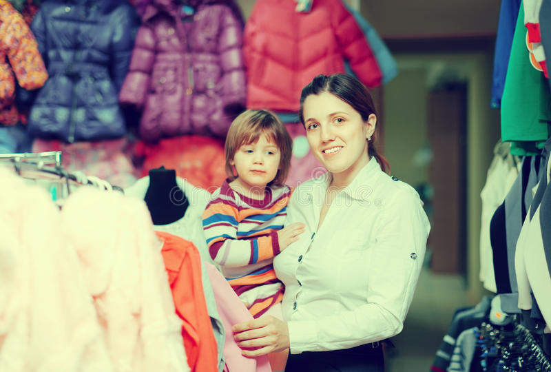 Mother with baby at clothes store. Joyful mother with baby girl chooses wear at clothes store. Focus on woman stock image