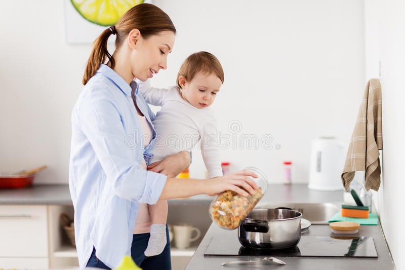 Mother and baby cooking pasta at home kitchen royalty free stock photo