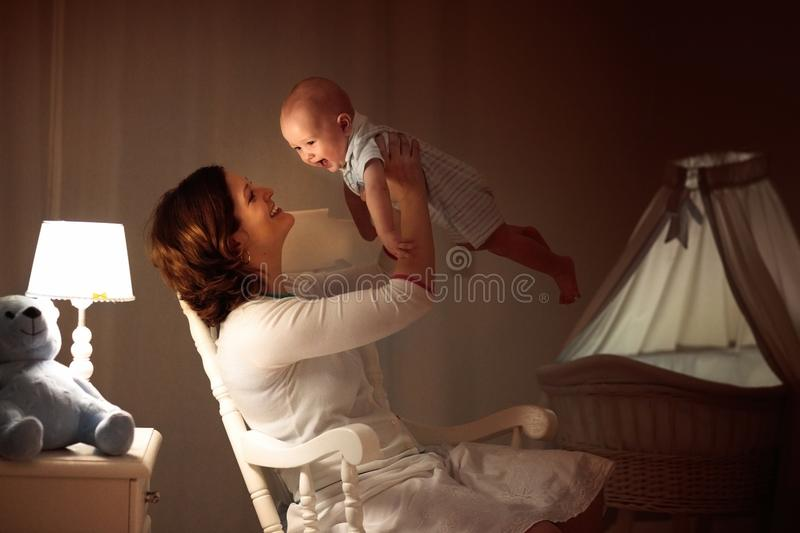 Mother and baby in dark bedroom royalty free stock image
