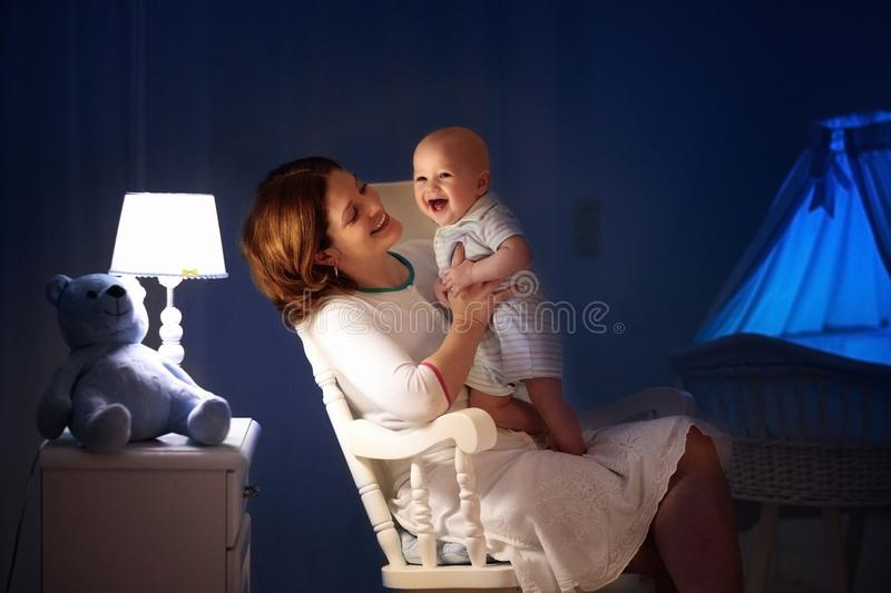 Mother and baby in dark bedroom royalty free stock photography