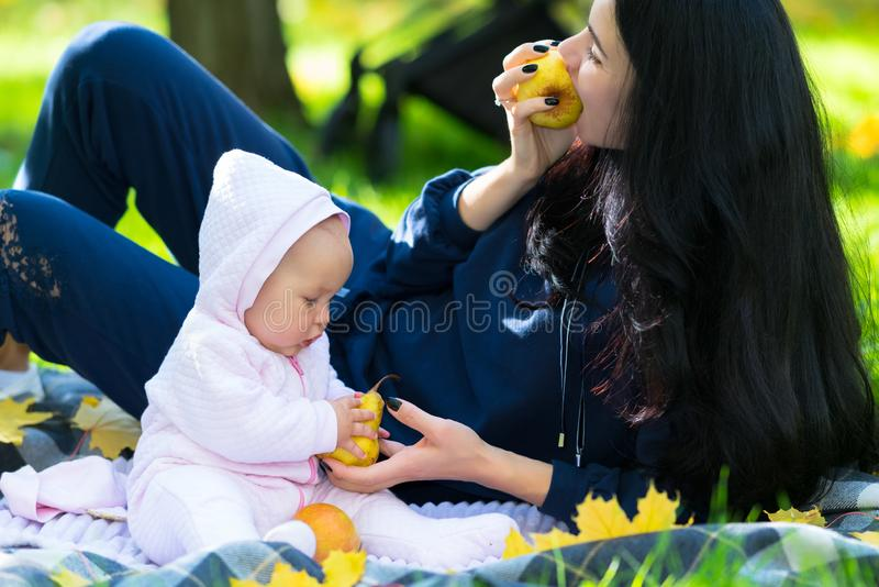 Mother and baby daughter eating fresh fall apples. Mother and baby daughter eating fresh fall apples on a blanket outdoors in a park or garden in a close up royalty free stock photos