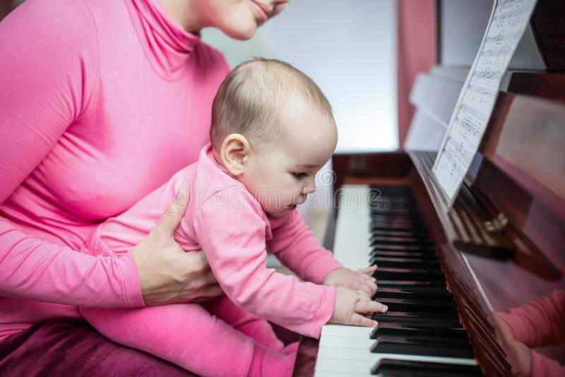 Mother And Baby Daughter Playing Piano At Home royalty free stock photography