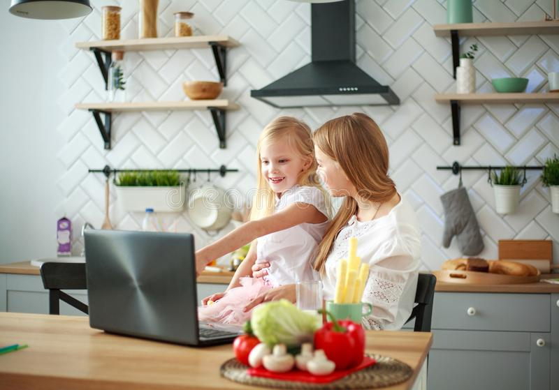 Mother with baby daughter sitting at table with groceries in kitchen with laptop stock photography