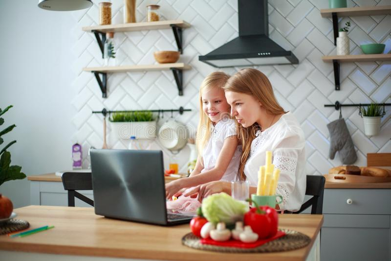 Mother with baby daughter sitting at table with groceries in kitchen with laptop royalty free stock images