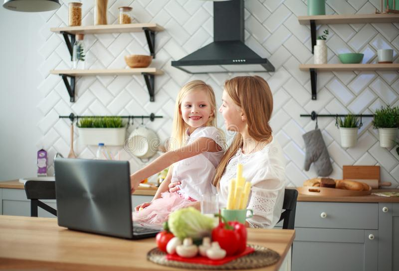 Mother with baby daughter sitting at table with groceries in kitchen with laptop royalty free stock photos