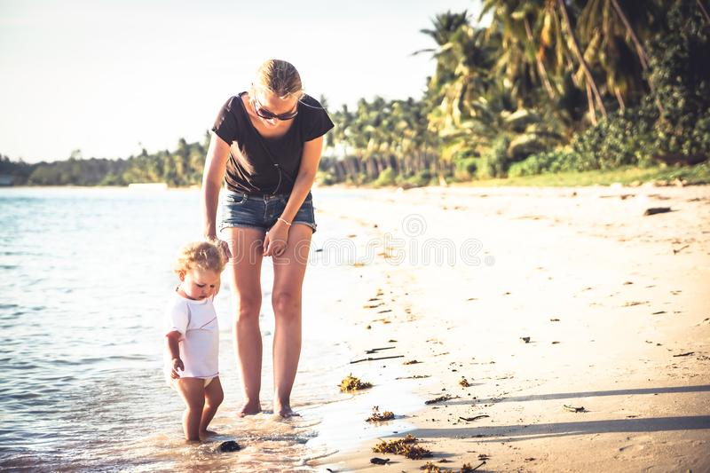 Mother and baby daughter walking on beach with holding hands royalty free stock photo