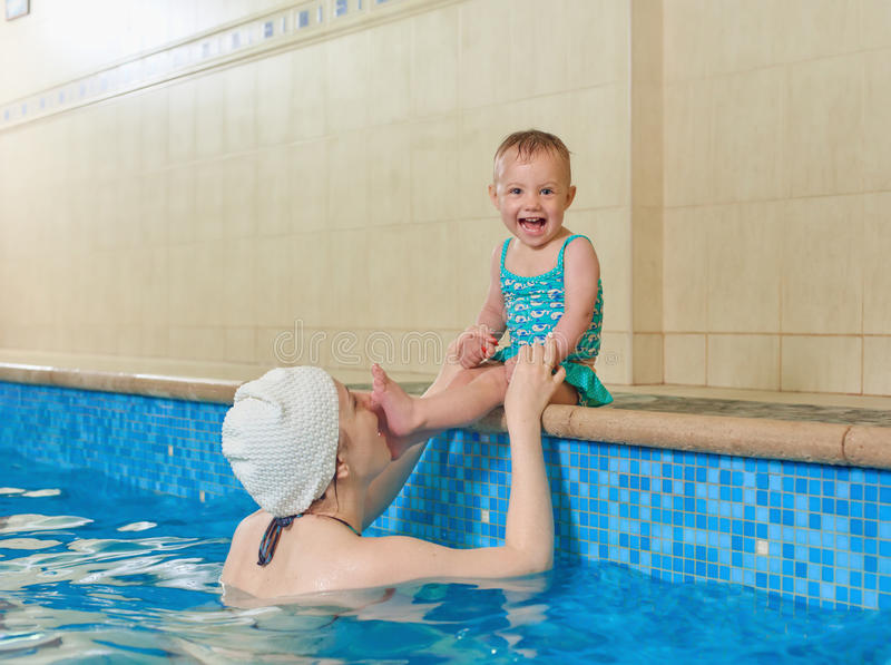 Mother and baby before dive swimming. Adorable baby girl enjoying swimming in a pool with her mother, early development class for infants teaching children to royalty free stock images
