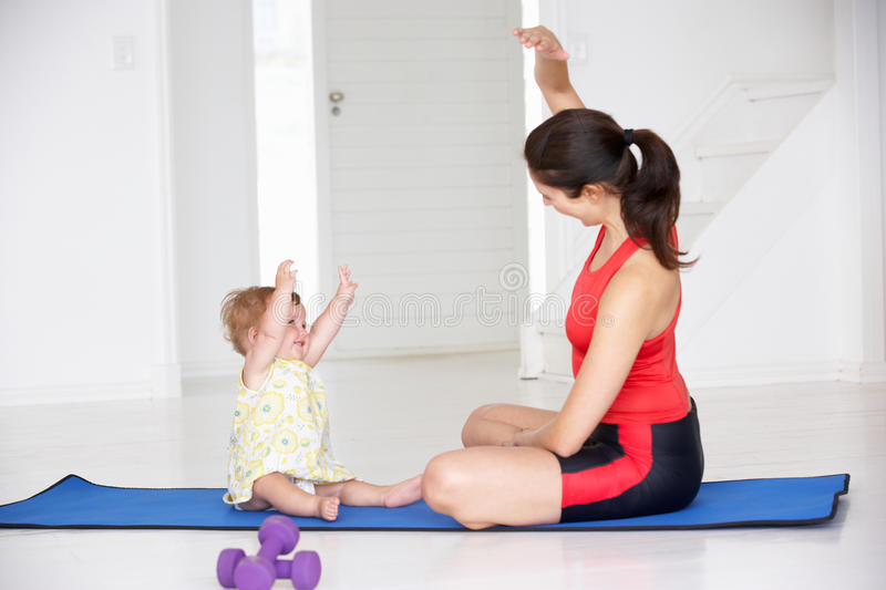 Mother and baby doing yoga. With hands in the air