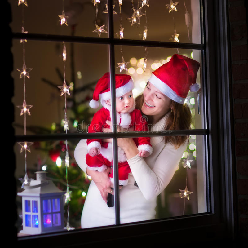 Mother and baby dressed as Santa at a window on Christmas stock photo
