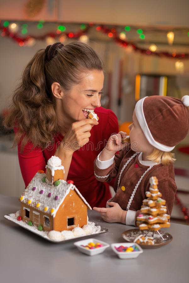 Mother and baby eating cookie in kitchen royalty free stock images
