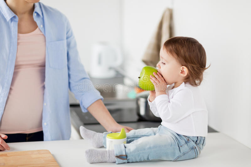 Mother and baby eating green apple at home kitchen stock photo