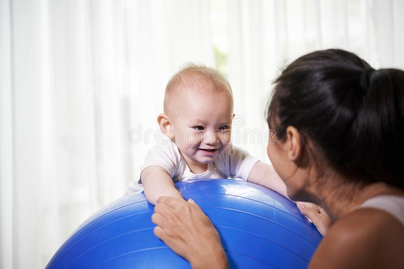 Mother and baby exerciging with fitness ball. Happy smiling baby boy enjoying exercising with his mother on big fitness ball at home royalty free stock images