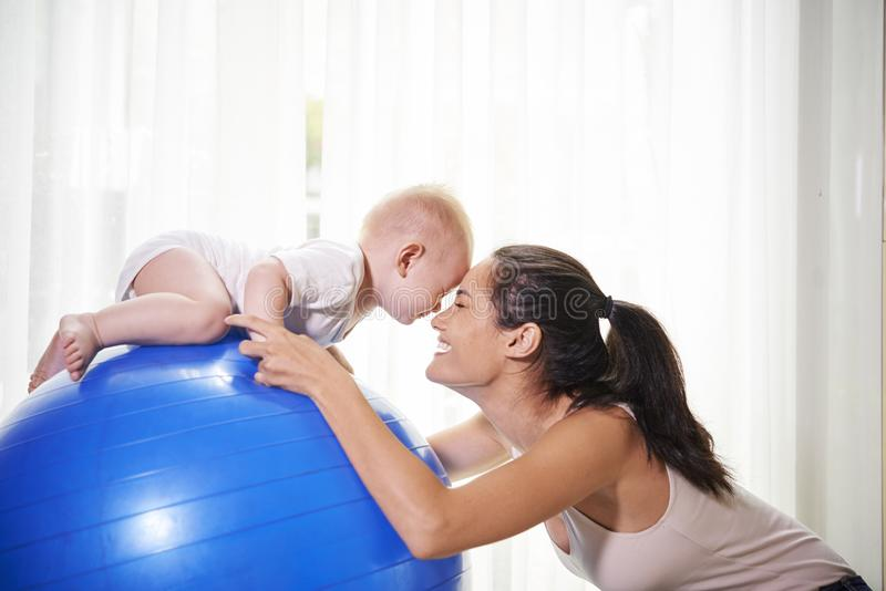 Mother and baby exercising at home. Happy slim young mother exrcising on fitness ball with her baby boy at home royalty free stock photography