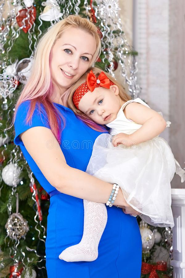 Mother with baby girl in front of xmas tree. Christmas family portrait. royalty free stock photos