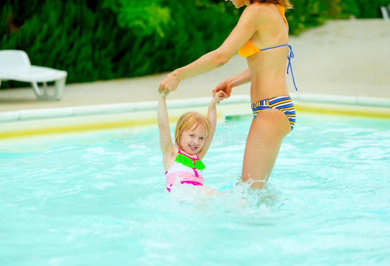 Mother and baby girl playing in swimming pool. Mother and happy baby girl playing in swimming pool stock images