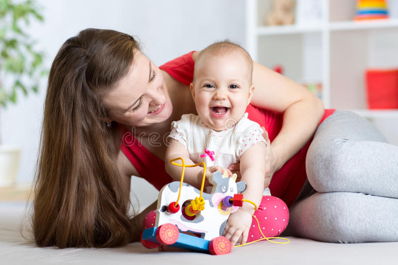 Mother and baby girl playing with toy in living room stock images