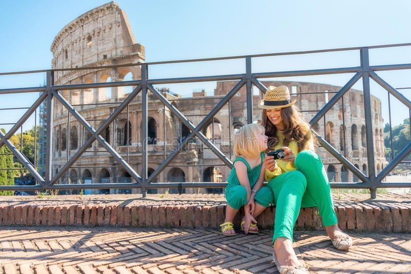 Mother and baby girl sitting in front of colosseum. In rome, italy stock photography