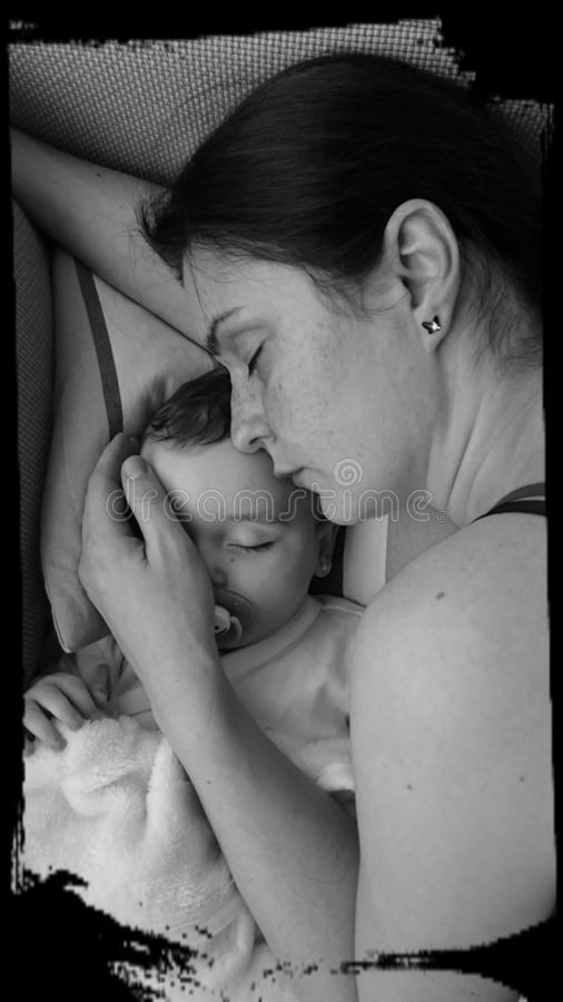 Mother and baby girl sleeping. Black and white portrait of a mother offering comfort and protection to her baby girl while sleeping tougher stock photos