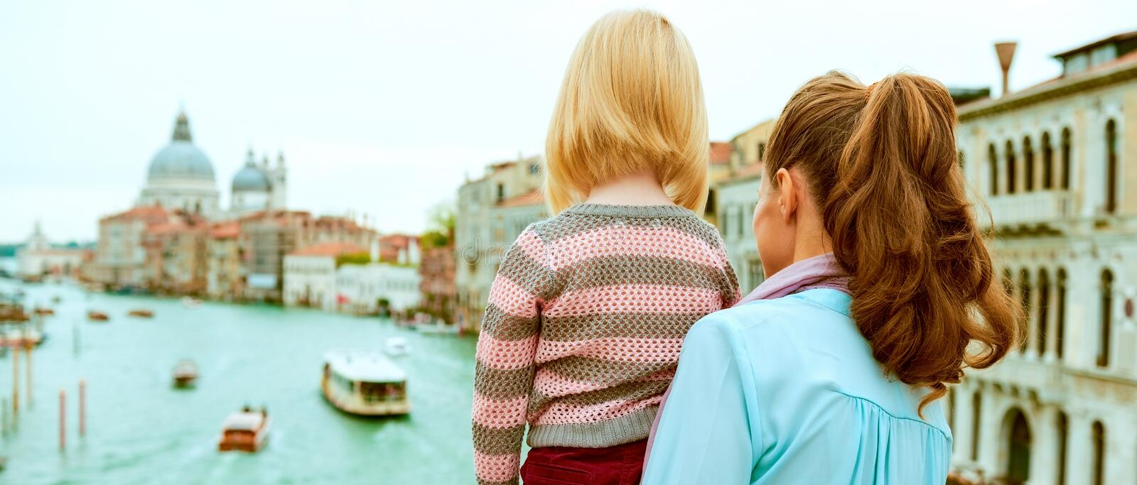Mother and baby girl standing on bridge with grand canal, Venice royalty free stock photos