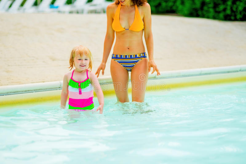 Mother and baby girl standing in pool. Mother and happy baby girl standing in pool stock photo