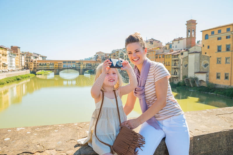 Mother and baby girl taking photo in florence. Mother and baby girl taking photo while standing on bridge overlooking ponte vecchio in florence, italy stock photo