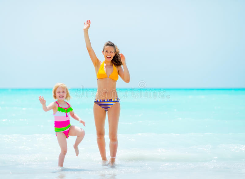 Mother and baby girl waving with hand. On sea coast royalty free stock images
