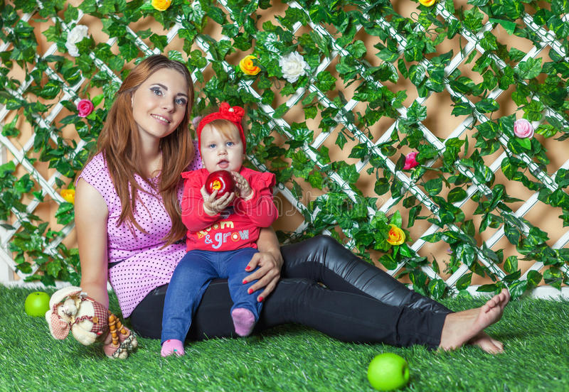 Mother with baby on hand sitting on the grass in the flower garden on a sunny summer day and eat apples. royalty free stock photo