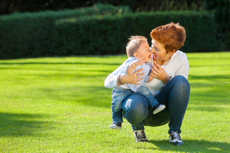 Mother and baby play on the grass royalty free stock images