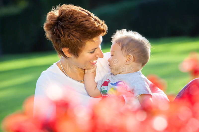 Mother and baby play on the grass royalty free stock image