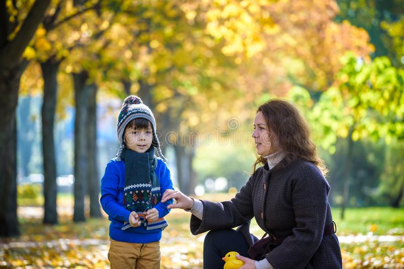 Mother and baby play in autumn park. Parent and child walk in the forest on a sunny fall day. Children playing outdoors with stock photo