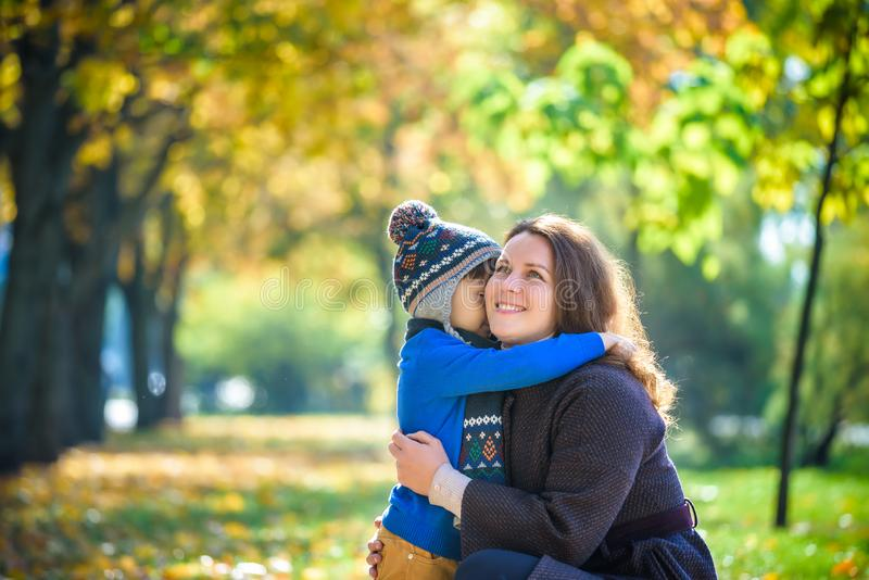 Mother and baby play in autumn park. Parent and child walk in th. E forest on a sunny fall day. Children playing outdoors with yellow maple leaf. Toddler boy stock photos