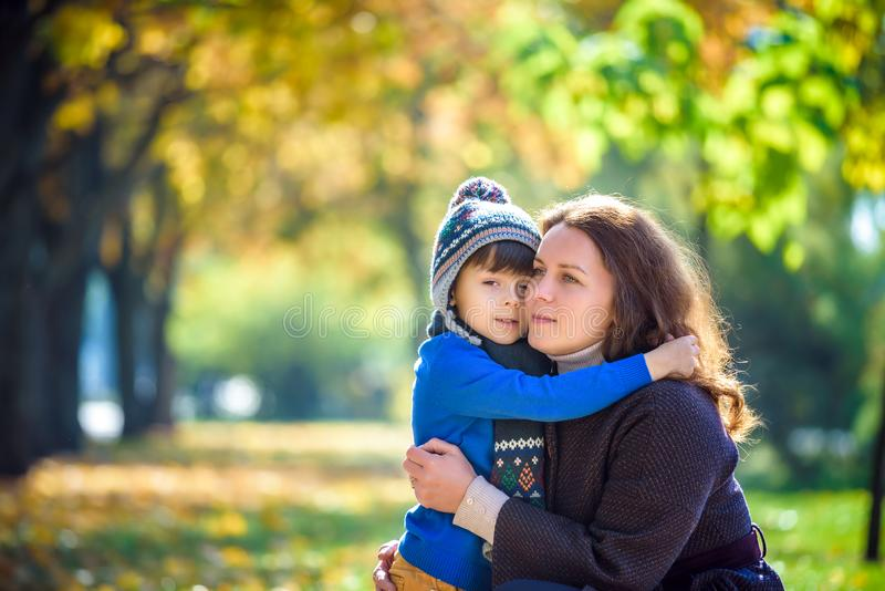 Mother and baby play in autumn park. Parent and child walk in th. E forest on a sunny fall day. Children playing outdoors with yellow maple leaf. Toddler boy stock image