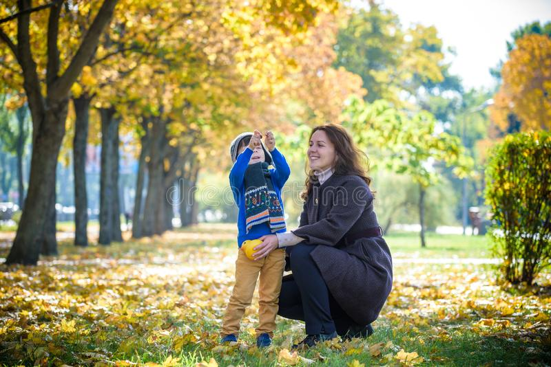 Mother and baby play in autumn park. Parent and child walk in th. E forest on a sunny fall day. Children playing outdoors with yellow maple leaf. Toddler boy royalty free stock photography