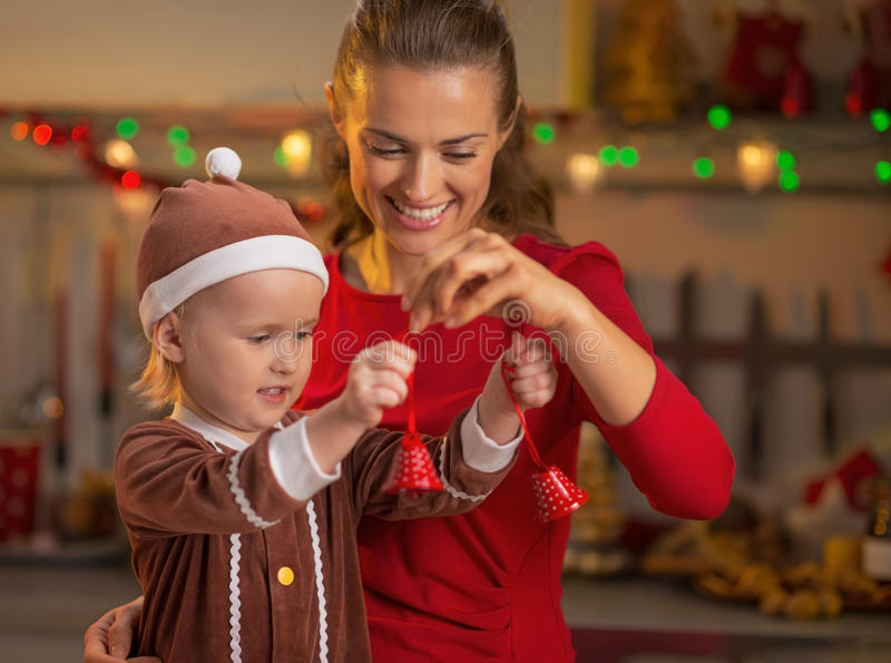 Mother and baby playing with christmas bells royalty free stock image