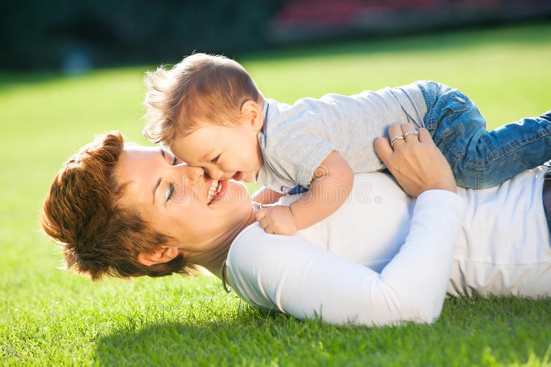 Mother and baby play on the grass royalty free stock photography