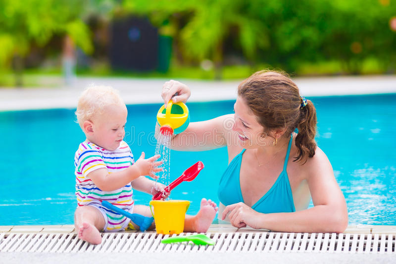Mother and baby playing in swimming pool. Happy family, young active mother and adorable curly little baby having fun in a swimming pool, playing with toy royalty free stock images