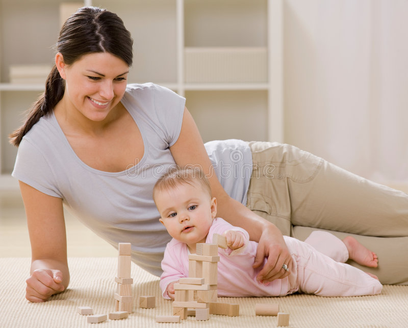 Mother and baby playing with wooden blocks royalty free stock photos