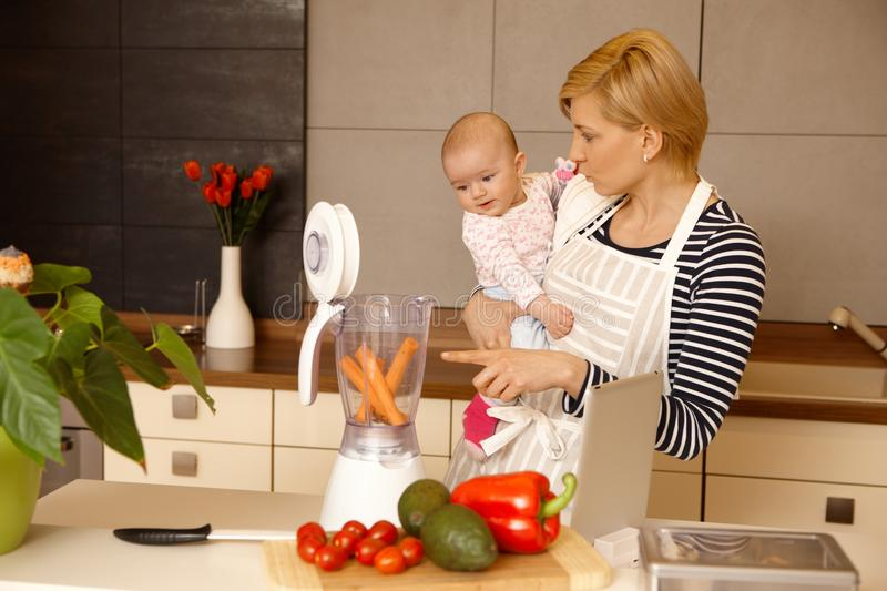 Mother and baby preparing food. Young mother holding baby girl in arms, preparing food together in kitchen royalty free stock photo