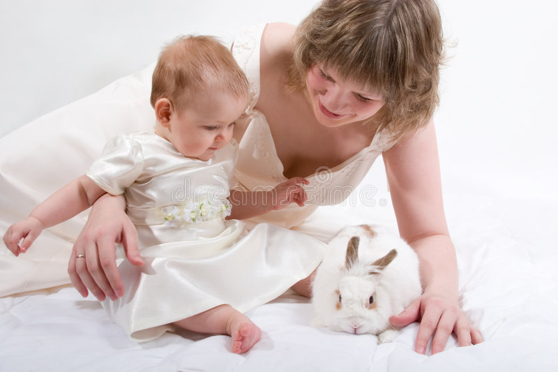 Mother and baby with rabbit. Mother and baby are playing with rabbit royalty free stock image