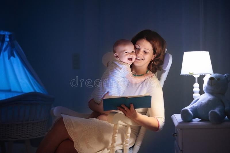 Mother reading a book to little baby stock image